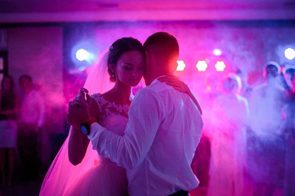 Brautpaar tanzt den Eröffnungstanz in leichtem Nebel und mit lila LED Beleuchtung. Ein zusaztoption in unserem Hochzeits DJ Paket.